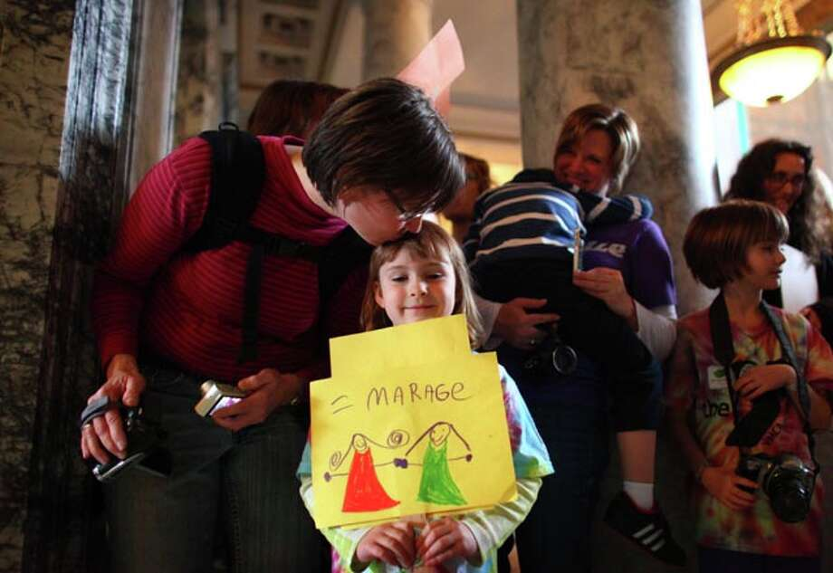 A young supporter holds a sign supporting same-sex marriage as the Washington House of Representatives passes marriage equality legislation earlier this year.  Washington votes on Referendum 74 on Tuesday.    / SEATTLEPI.COM