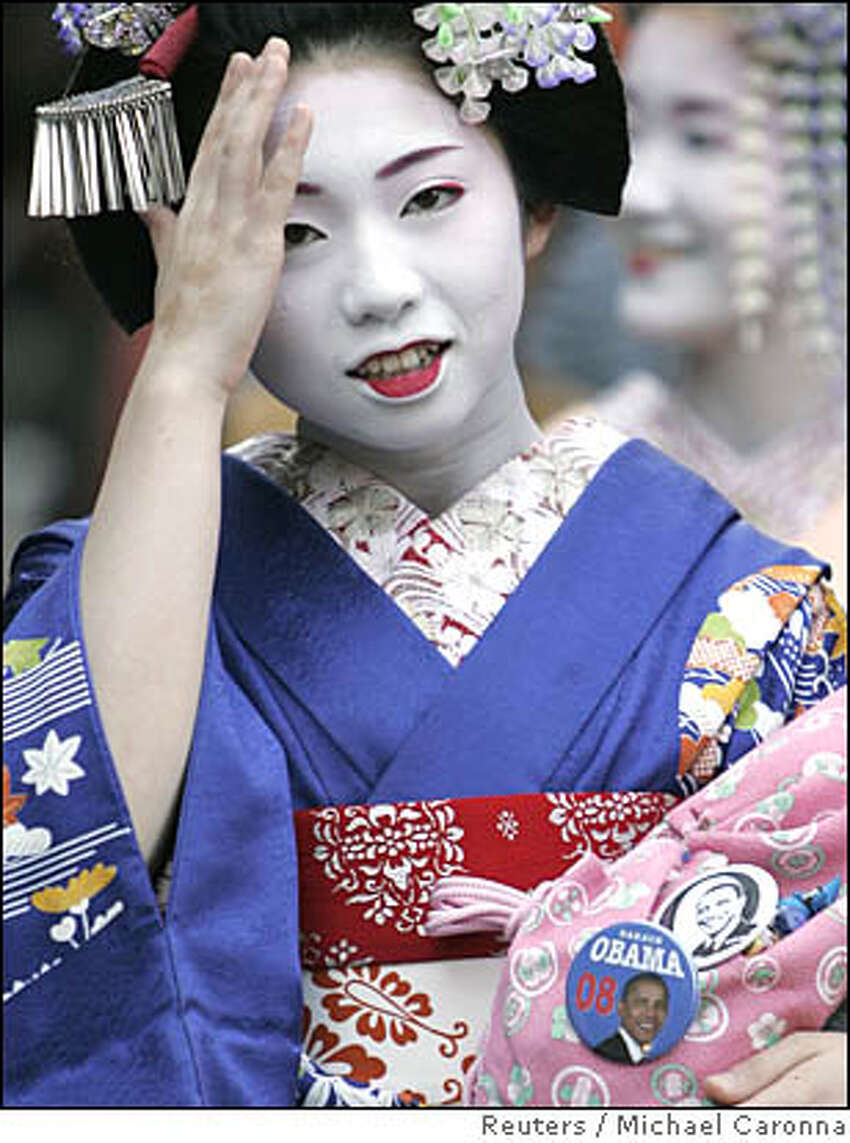 Woman dressed as a maiko walks down a street wearing Barack Obama campaign buttons