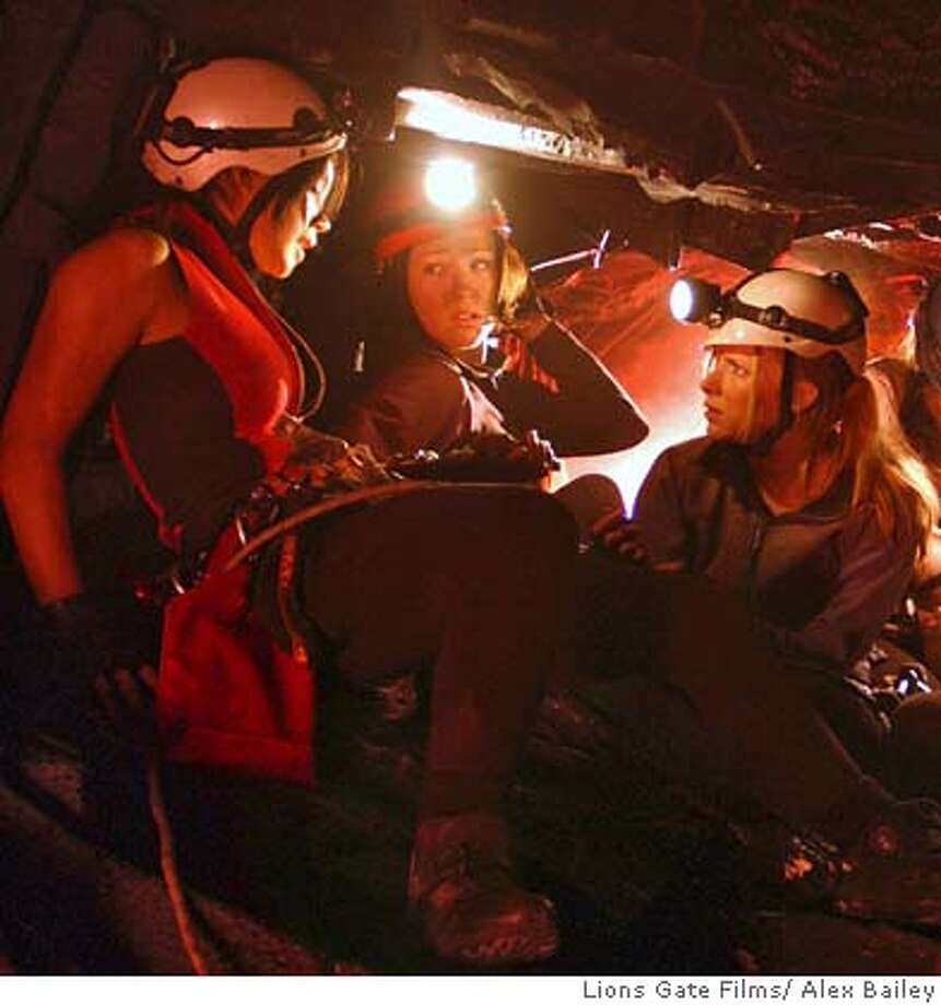 In this photo provided by Lions Gate Films, three friends Juno (Natalie Mendoza), Beth (Alex Reid) and Sarah (Shauna Macdonald) are lost in a unexplored cave and look for a way out only to discover a race of monstrous humanoid creatures that are adapted perfectly to life in the dark in 'The Descent.' (AP Photo/Lions Gate Films/ Alex Bailey) Photo: Lions Gate Films/ Alex Bailey