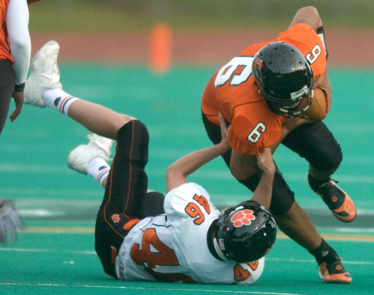 Ridgefield's Duncan Cozens, left, sacks Stamford's Jalen Holmes, right, during an FCIAC football game against Ridgefield High School at Stamford High School in Stamford, Conn. on Thursday, Sept. 17, 2009