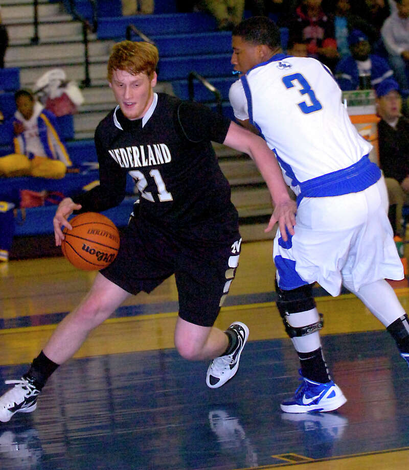 Nederland's Colton Weisbrod drives around Ozen's Trey Green at Ozen High School in Beaumont, Friday, February 10, 2012. Tammy McKinley/The Enterprise Photo: TAMMY MCKINLEY