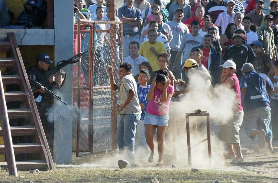 Inmates' relatives clash with police outside a prison after a deadly fire in Comayagua, Honduras, 90 miles (140 kilometers) north of the capital, Tegucigalpa, Honduras, Wednesday Feb. 15, 2012. At least 300 inmates were killed and 21 are injured, according to authorities. (AP Photo/Fernando Antonio) Photo: Fernando Antonio / AP