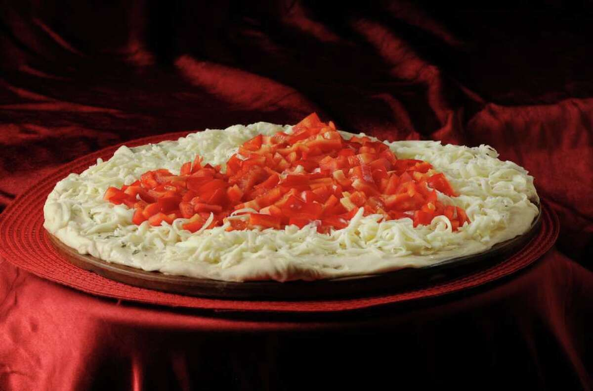 Pizza with red peppers before it goes into the oven. (Will Waldron / Times Union)