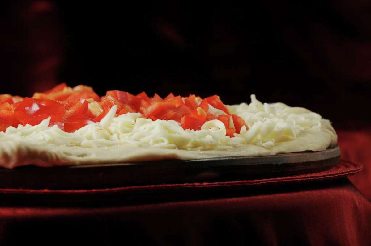 Pizza with red peppers by before it goes into the oven. (Will Waldron / Times Union)