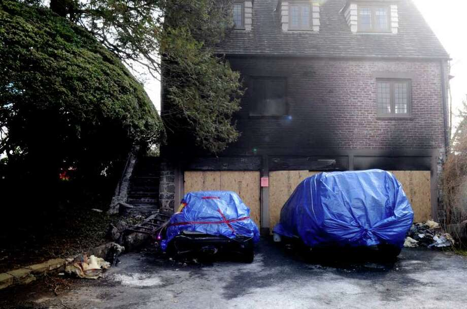 A Sunday night fire at 22 Alden Road in central Greenwich burned a home's three-car garage, pictured here Tuesday, Feb. 14, 2012. The fire began in a Mini Cooper parked in the garage, a fire official said Wednesday. Photo: Helen Neafsey / Greenwich Time