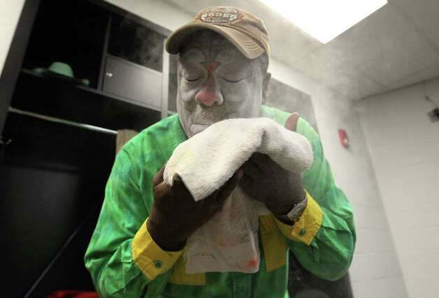 Barrelman Leon Coffee uses baby powder to set the makeup on his face before taking part in the 2012 San Antonio Stock Show & Rodeo on Tuesday, Feb. 14, 2012. Coffee said he has kept for the same design on his face for years. Photo: Kin Man Hui, San Antonio Express-News / San Antonio Express-News