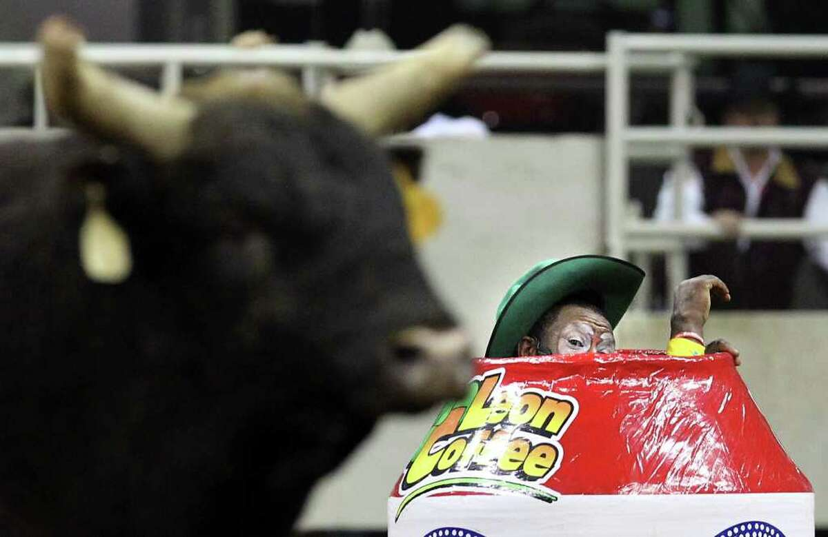 Barrel man Leon Coffee peers out at a bull that passes by during the bull riding competition at the 2012 San Antonio Stock Show & Rodeo on Tuesday, Feb. 14, 2012. Coffee has been working in rodeos as a bullfighter since 1969. These days he relies on younger, quicker help with the bulls while he works the crowd from his barrel during the bull riding competitions. Coffee said though his job is to entertain the crowd, his main concern is for the cowboys.