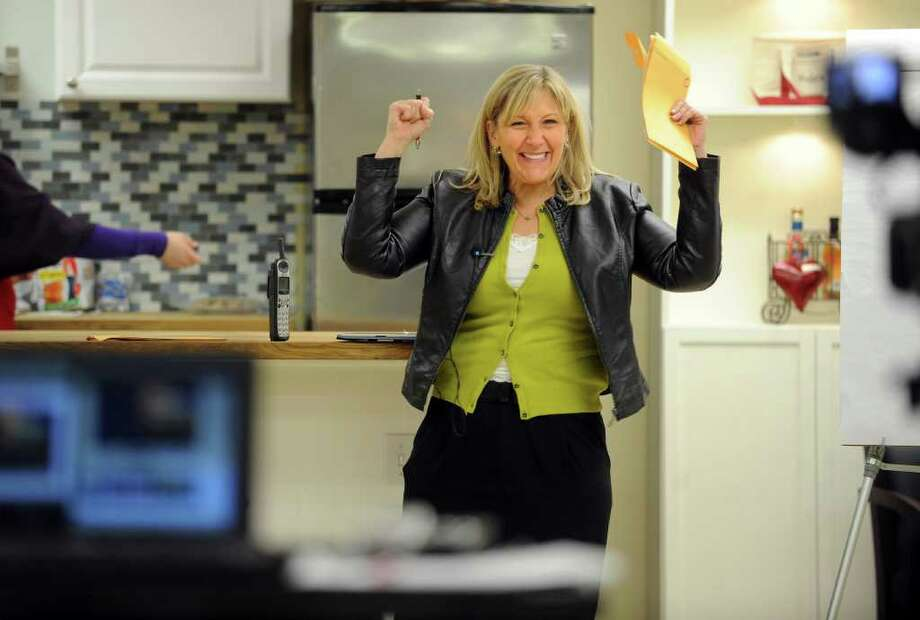 Weight loss guru Kim Bensen applauds a client's progress during a live-streaming meeting with corporate clients at her weight loss center in Shelton, Conn.  Bensen conducts weekly meetings with local clients but also offers her services to clients from all over the world who participate online. Photo: Autumn Driscoll / Connecticut Post