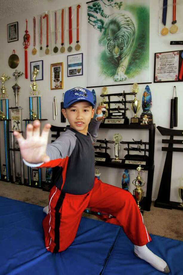 In this 2008 photo, Moshe Kai Cavalin, 10, strikes a martial arts position at his home studio. Photo: Damian Dovarganes / AP2008