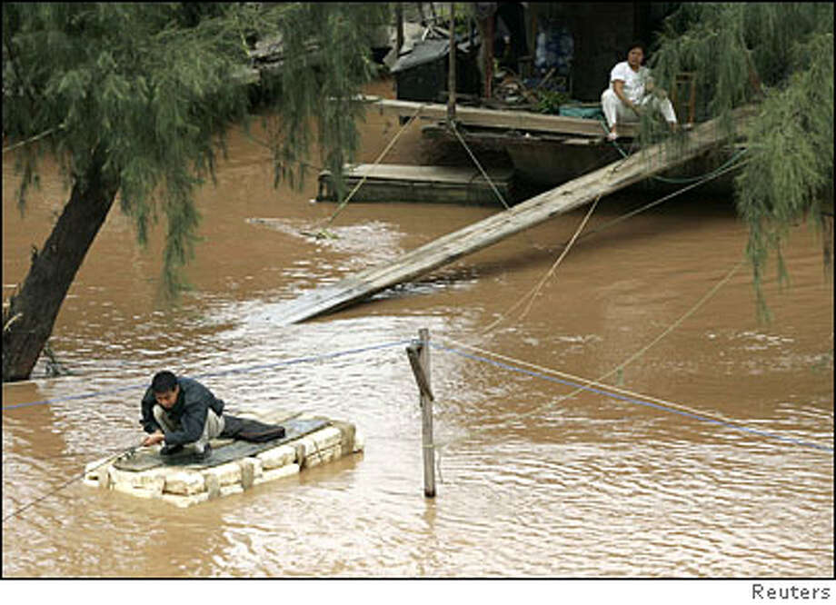 A resident uses power cables to move on a home-made boat on a flooded street in Nanning Photo: STRINGER SHANGHAI