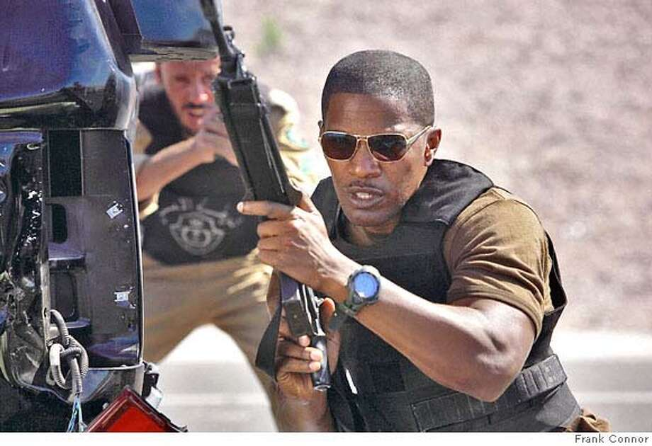 FBI team leader Ronald Fleury (JAMIE FOXX) steadies his weapon in a timely thriller that tracks a powder-keg criminal investigation shared by two cultures chasing a deadly enemy ready to strike again: ?The Kingdom?. Photo: Photo Credit: Frank Connor