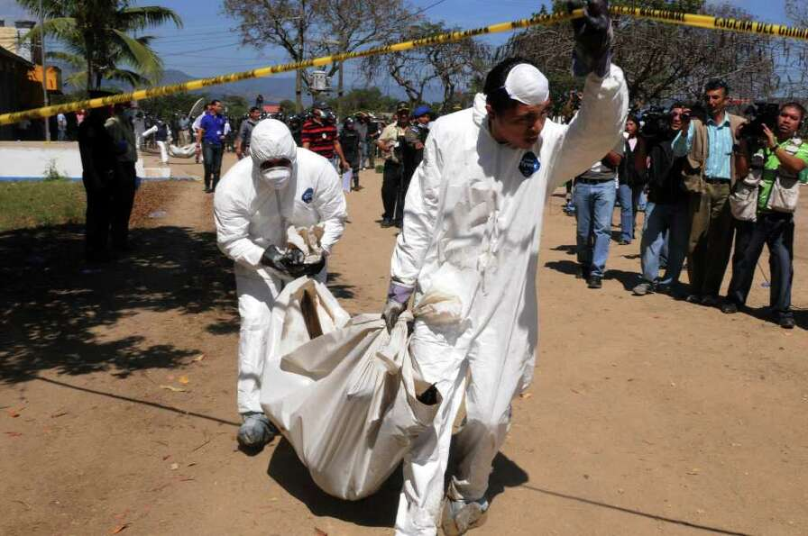 Forensic personnel remove the corpse of one of the inmates of by the National Prison compound in Com