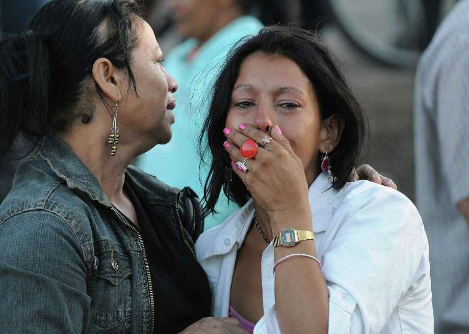 Inmates' relatives stand outside a prison after a fire broke out inside in Comayagua, Honduras, 90 miles (140 kilometers) north of the capital, Tegucigalpa, Honduras, early Wednesday Feb. 15, 2012. Photo: Fernando Antonio, Associated Press / AP
