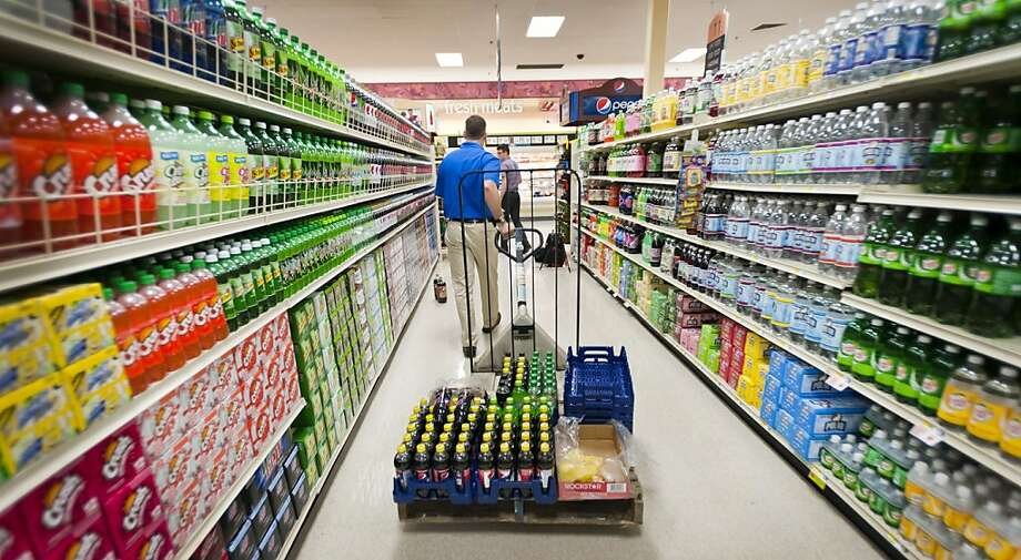 An employee of PepsiCo, which is batting Coca-Cola over orange juice, delivers drinks to a store. Photo: Paul Taggart, Bloomberg