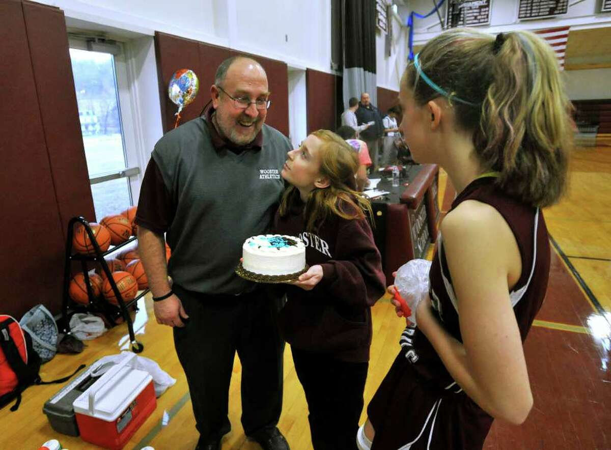 Wooster coach David MacNutt reacts to his daughter, Jamie, center, bringing him a cake celebrating him on his 700th win as MacNutt's other daughter, Kate, watches after beating Marvelwood 48-27 at Wooster School in Danbury on Wednesday, Feb. 15, 2012.