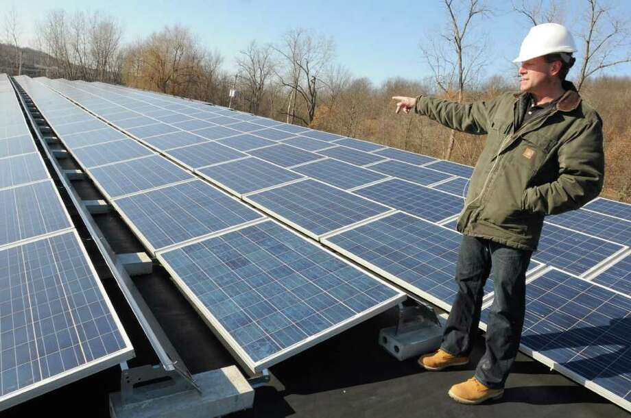 Steven Erby, vice president of Monolith Solar Associates, LLC, shows off solar panels his company installed equalling about 50, 000 watts of power on the roof of DiSiena Furniture on Thursday, Feb. 9, 2012 in Mechanicville, N.Y.  There are 231 panels of 230 watts each on this roof.  (Lori Van Buren / Times Union) Photo: Lori Van Buren