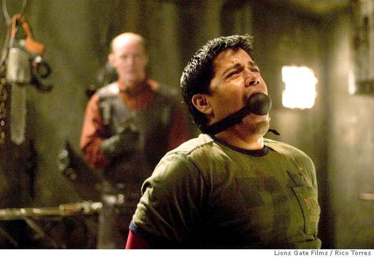 """Actor Jay Hernandez (R) appears in a scene from the new film """"Hostel"""" in this undated publicity photograph. The film, directed by Eli Roth, features brutal scenes of torture and violence and is about three backpackers who head to a Slovakian city that promises to meet their hedonistic expectations, with no idea of the horror that awaits them. The film opens on Thursday in the U.S. NO ARCHIVES REUTERS/Rico Torres/Lions Gate Films/Handout Lions Gate Films / Rico Torres 0"""