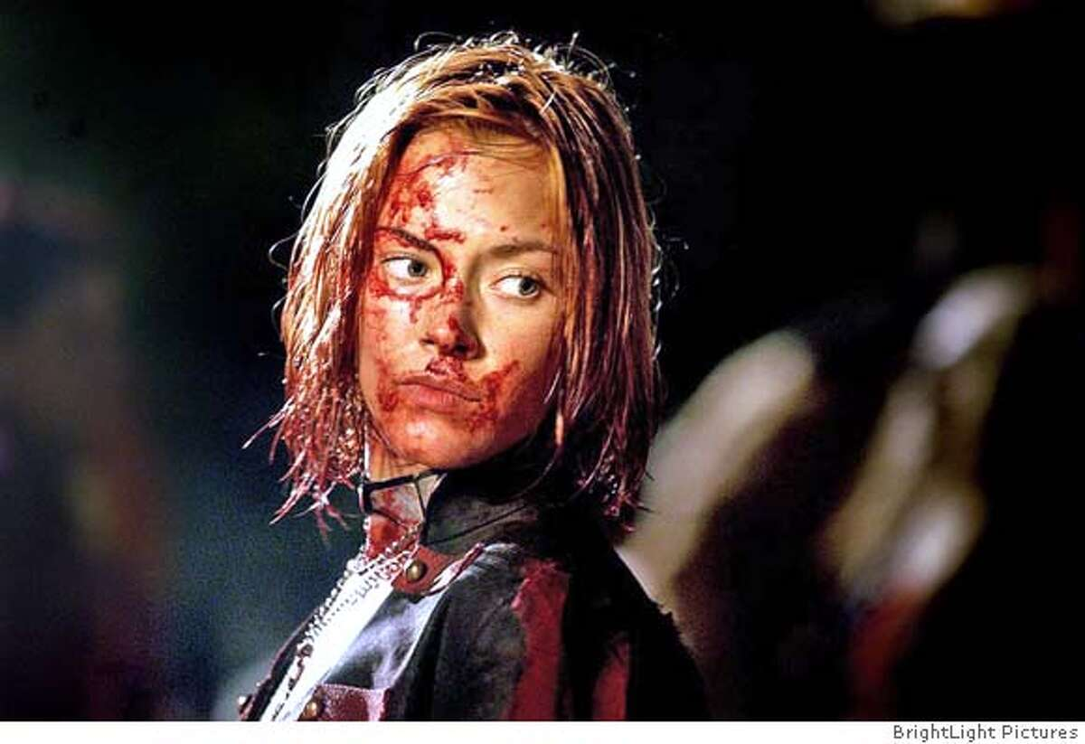 """Actress Kristanna Loken portrays character """"Rayne"""", a dhampir half-human, half-vampire prone to fits of blind blood rage but saddled with a compunction for humans, who is trying to avenge her mother's rape by her father, in a scene from the new film """"BloodRayne"""" in this undated publicity photograph. The film opens in the United States January 6, 2006. NO ARCHIVES REUTERS/BrightLight Pictures/Handout 0"""