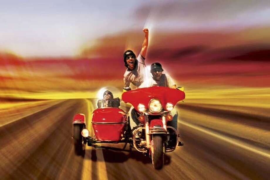 "Ami Ankilewitz rides in the sidecar as his friend Asaf raises a fist to the sky. They are accompanied by their expert Harley Davidson driver on a road trip across the country in the film ""39 POUNDS OF LOVE."" Ran on: 12-04-2005 Photo: XX"