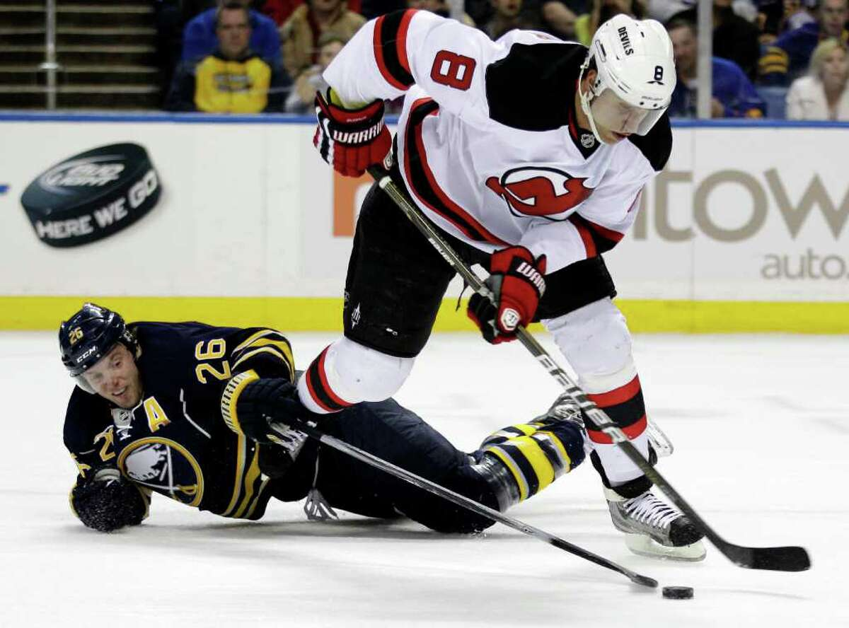 Buffalo Sabres' Thomas Vanek (26), of Austria, battles for the puck with New Jersey Devils' Dainius Zubrus (8), of Lithuania, during the first period of an NHL hockey game in Buffalo, N.Y., Tuesday, Feb. 14, 2012. (AP Photo/David Duprey)