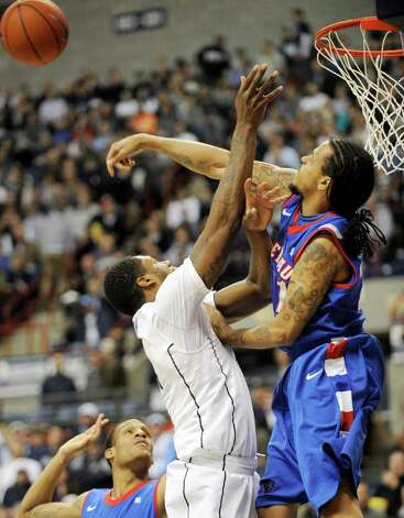 DePaul's Jamee Crockett blocks a shot by Connecticut's Alex Oriakhi during the first half of an NCAA college basketball game in Storrs, Conn., on Wednesday, Feb. 15, 2012. (AP Photo/Fred Beckham) Photo: Fred Beckham/Associated Press / FR153656 AP