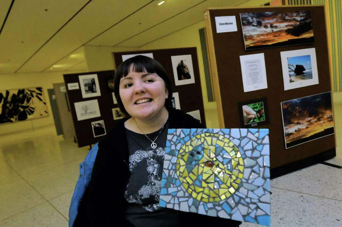 Twenty-one year old Sara Orleanski of Johnstown shows off her piece in the Brain Injury Association of New York State annual art show at the South Concourse of the Empire State Plaza in Albany, New York Wednesday Feb.15, 2012.Sara was 15 when she sustained a traumatic brain injury (TBI) in a near-fatal car accident. After months in a coma, years in a wheelchair, and untold hours of intensive rehabilitation, Sara has started to remake her life. In fact, she and her parents participated in a documentary film about children with brain injury, called ?Keep Moving Forward,? which is available on the Association?s website.( Michael P. Farrell/Times Union)