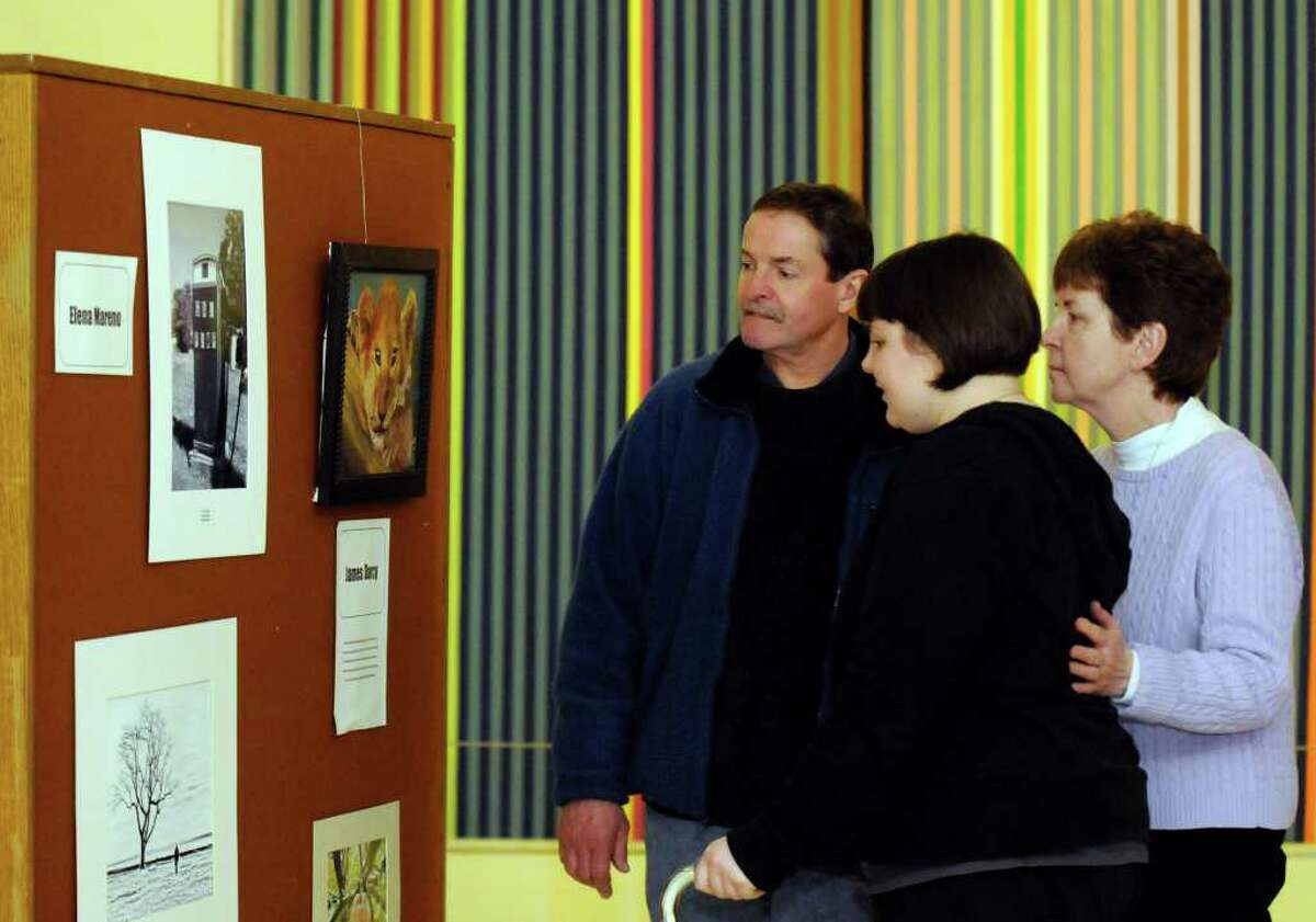 Twenty-one year old Sara Orleanski of Johnstown looks over the show she is in, the Brain Injury Association of New York State annual art show, with her parents Ken and Kathy Orleanski at the South Concourse of the Empire State Plaza in Albany, New York Wednesday Feb.15, 2012.Sara was 15 when she sustained a traumatic brain injury (TBI) in a near-fatal car accident. After months in a coma, years in a wheelchair, and untold hours of intensive rehabilitation, Sara has started to remake her life. In fact, she and her parents participated in a documentary film about children with brain injury, called ?Keep Moving Forward,? which is available on the Association?s website.( Michael P. Farrell/Times Union)