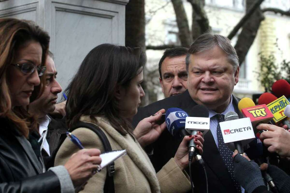 Greek Finance Minister Evangelos Venizelos, right, speaks to the press after a meeting with the Greek President Karolos Papoulias in Athens Wednesday, Feb. 15, 2012. Greece's finance minister said that all pending issues in its international creditors' requirements for the country's second bailout will be completed ahead of a Wednesday evening conference call between eurozone finance ministers. Venizelos made the comments after a meeting with President Karolos Papoulias, who he said will give up his presidential salary to help in the crisis.(AP Photo/Petros Giannakouris)