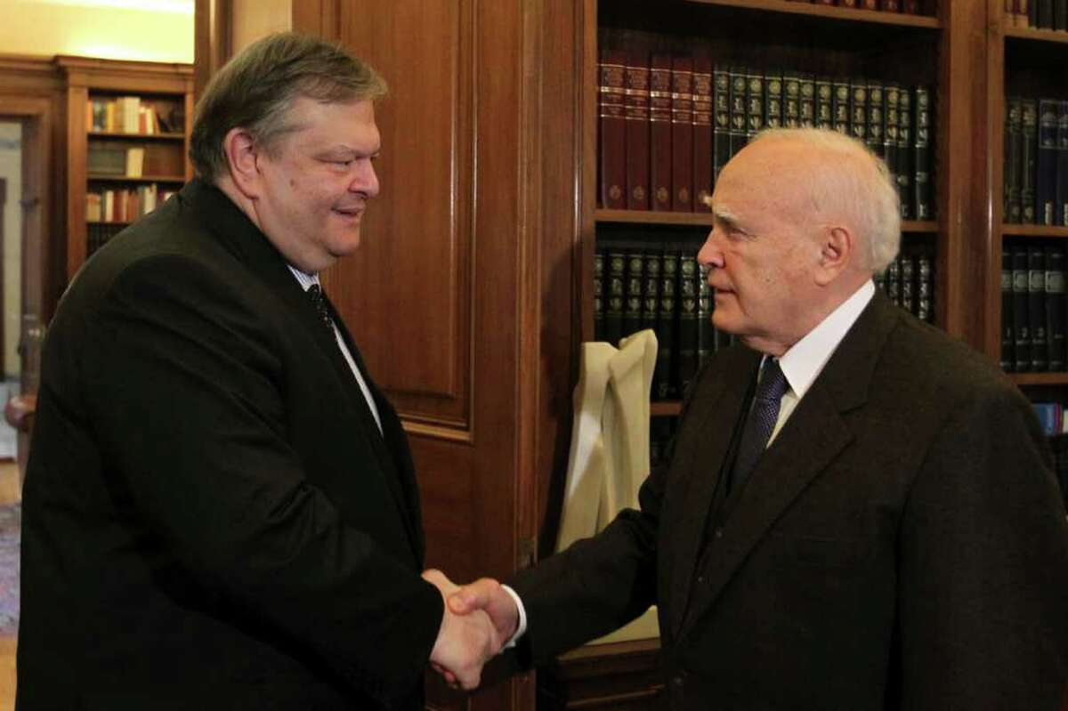 Greek Finance Minister Evangelos Venizelos, left, shakes hands with Greek President Karolos Papoulias, during their meeting at the Presidential palace in Athens, on Wednesday, Feb. 15, 2012. Greece's finance minister said that all pending issues in its international creditors' requirements for the country's second bailout will be completed ahead of a Wednesday evening conference call between eurozone finance ministers.Venizelos made the comments after a meeting with President Karolos Papoulias, who he said will give up his presidential salary to help in the crisis.(AP Photo/Petros Giannakouris)