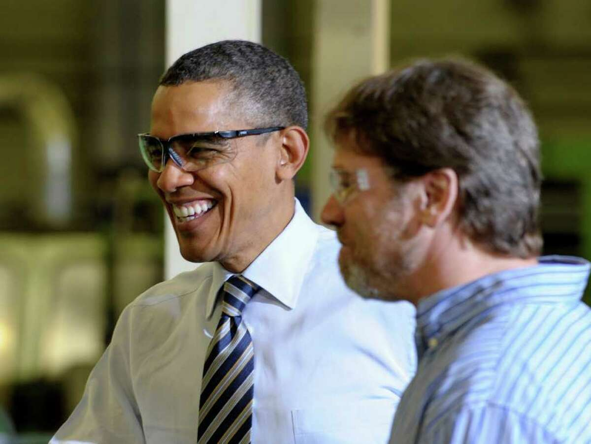 President Barack Obama talks with Master Lock employee Eric Hammerer while visiting Master Lock in Milwaukee, Wednesday, Feb. 15, 2012. Obama is visiting the Master Lock manufacturing operation before heading on a three-day trip to the West Coast. (AP Photo/Susan Walsh)