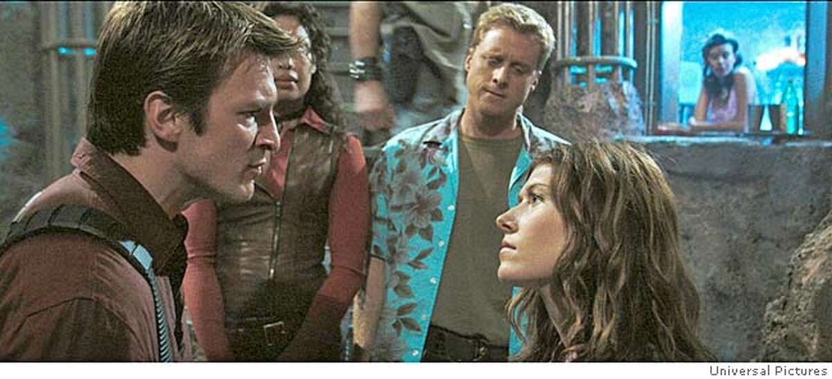 SERENITY30 Writer/Director Joss Whedon makes his feature film directorial debut with the futuristic action-adventure Serenity. Trouble brews on ship as the crew of Serenity (L to R): GINA TORRES as Zoe, ALAN TUDYK as Wash and JEWEL STAITE as Kaylee argue with NATHAN FILLION (far left) as Captain Malcolm Reynolds. Credit: Universal Pictures