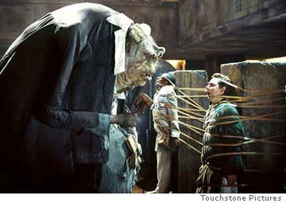 The alien Jeltz holds Ford Prefect (center, Mos Def) and Arthur Dent (Martin Freeman) captive. Photo courtesy of Touchstone Pictures