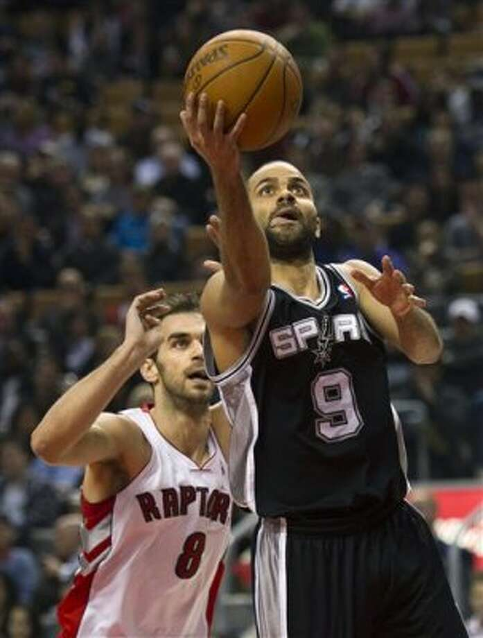 San Antonio Spurs guard Tony Parker, right, scores past Toronto Raptors guard Jose Calderon, left, during first-half NBA basketball game action in Toronto on Wednesday, Feb. 15, 2012. (AP Photo/The Canadian Press, Nathan Denette) (AP)