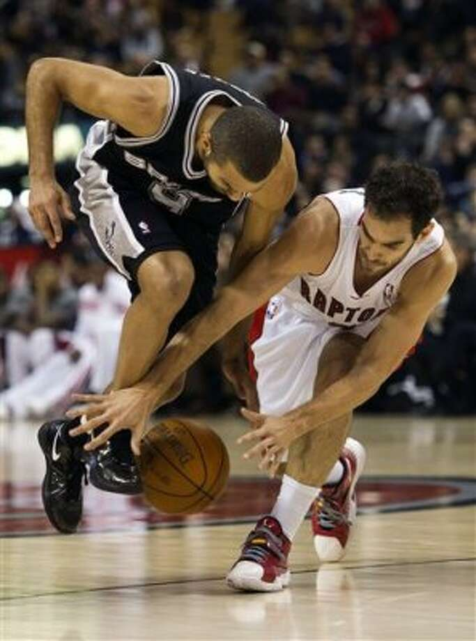 Toronto Raptors guard Jose Calderon, right, battles for the ball with San Antonio Spurs guard Tony Parker, left, during first-half NBA basketball game action in Toronto on Wednesday, Feb. 15, 2012. (AP Photo/The Canadian Press, Nathan Denette) (AP)
