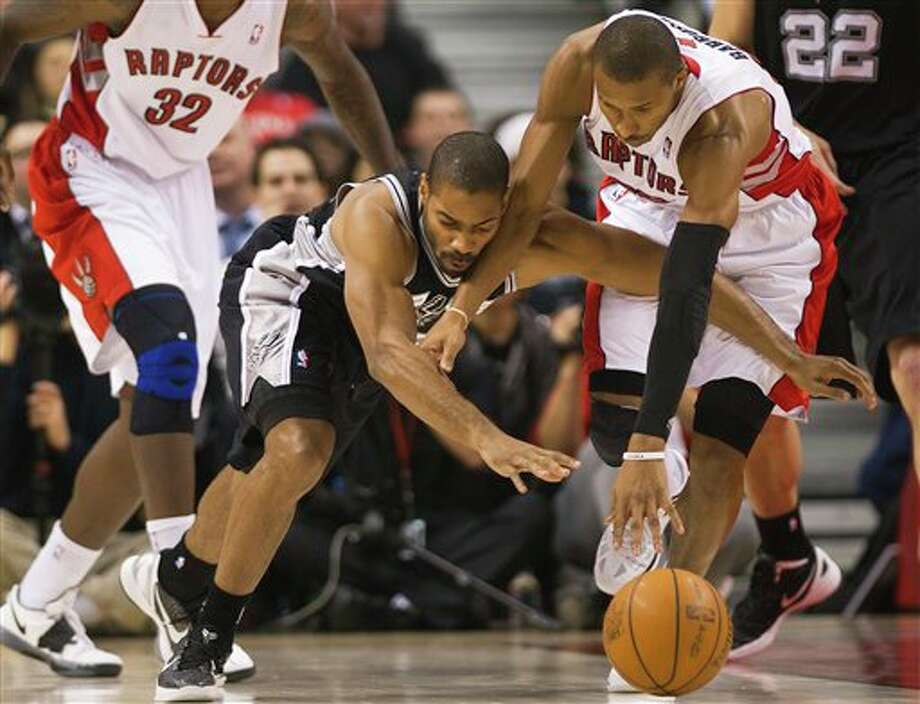 Toronto Raptors guard Leandro Barbosa, right, battles for the ball against San Antonio Spurs guard Gary Neal, left, during first-half NBA basketball game action in Toronto on Wednesday, Feb. 15, 2012. (AP Photo/The Canadian Press, Nathan Denette) Photo: Nathan Denette, AP / The Canadian Press