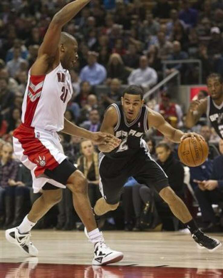 San Antonio Spurs guard Cory Joseph, right, drives past Toronto Raptors forward Jamaal Magloire, left,  during first-half NBA basketball game action in Toronto on Wednesday, Feb. 15, 2012. (AP Photo/The Canadian Press, Nathan Denette) (AP)