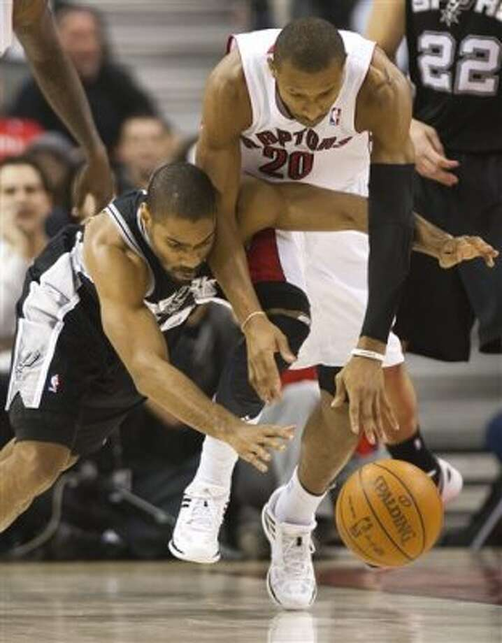 Toronto Raptors guard Leandro Barbosa, right, battles for the ball against San Antonio Spurs guard Gary Neal, left, during first-half NBA basketball game action in Toronto on Wednesday, Feb. 15, 2012. (AP Photo/The Canadian Press, Nathan Denette) (AP)
