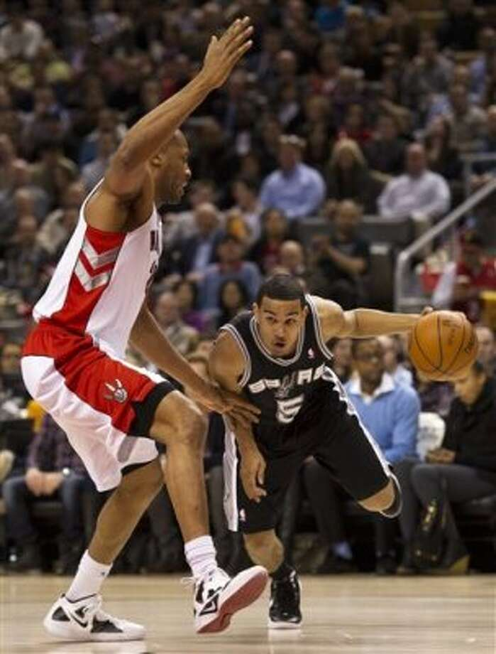 San Antonio Spurs guard Cory Joseph, right, drives past Toronto Raptors forward Jamaal Magloire during first-half NBA basketball game action in Toronto on Wednesday, Feb. 15, 2012. (AP Photo/The Canadian Press, Nathan Denette) (AP)