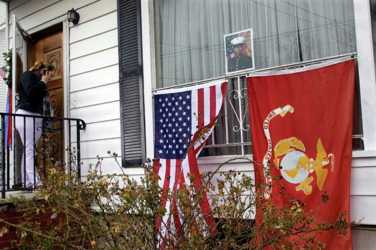 A photograph of U.S. Marine Lance Cpl Osbrany Montes De Ocha, 20, is seen in a window with American and U.S. Marines flags at the family home in North Arlington, N.J., Wednesday, Feb. 15, 2012, as a person arrives to pay respects. Osbrany Montes De Oca was killed in Afghanistan on Feb. 10. Osbrany is one of four brothers, three of whom are Marines. Older brother, Sandro Moreta, and Osmany, Osbrany Montes De Oca's twin, are also Marines. (AP Photo/Mel Evans)