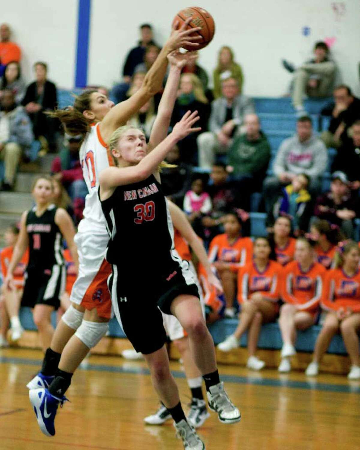 Danbury's Casey Smith blocks a shot by New Canaan's Kelly Armstrong (30) Wednesday night at Danbury High School. The victory enabled the Hatters to finish the regular season undefeated.