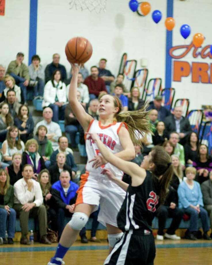 Danbury's Rachel Gartner is fouled by New Canaan's Georgia Hunsinger on a drive to the basket Wednesday night at Danbury High School. Photo: Barry Horn / The News-Times Freelance