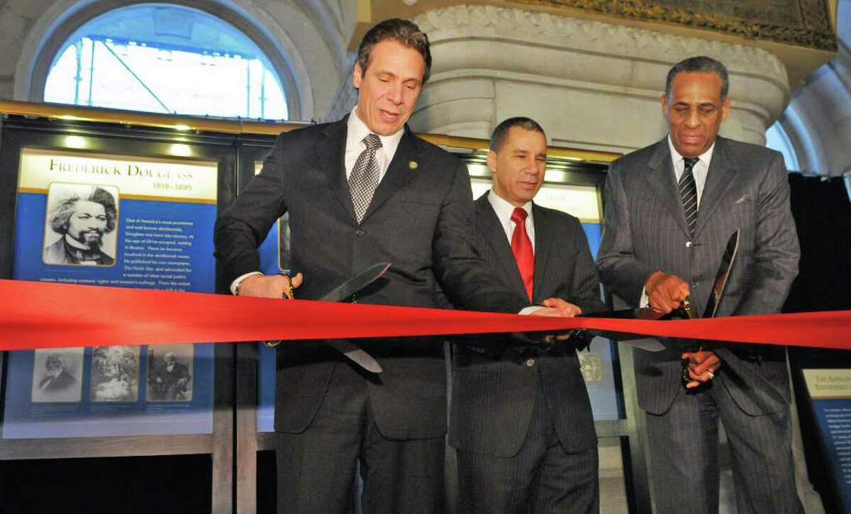 NYS Gov. Andrew Cuomo, left, former Gov. David Paterson and SUNY chairman H. Carl McCall, at right, cut a ribbon opening a Capitol exhibit honoring prominent African-American New Yorkers in recognition of Black History at the Capitol Wednesday Feb. 15, 2012. (John Carl D'Annibale / Times Union)