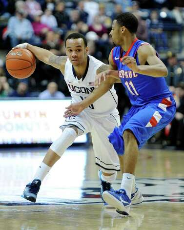 Connecticut's Shabazz Napier, left, drives past DePaul's Jeremiah Kelly during the first half  of  an NCAA college basketball game in Storrs, Conn., on Wednesday, Feb. 15, 2012. Connecticut won 80-54. (AP Photo/Fred Beckham) Photo: Fred Beckham, Associated Press / FR153656 AP