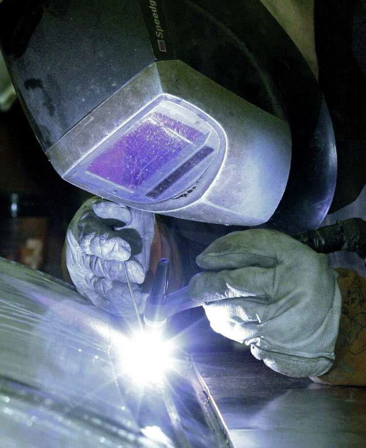 Factory workers, like this welder at JV Northwest in Camby, Ore., were lighting the way to production gains in December and January. Photo: Rick Bowmer / AP