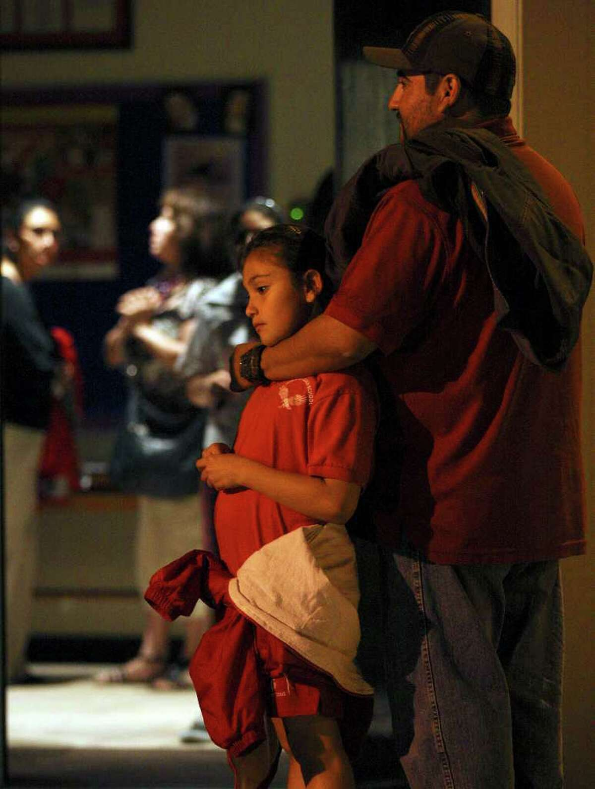 St. Philip of Jesus Catholic School third-grader Tessa Cantu, 8, gets a hug from her uncle, L. Ramirez, after parents and staff attended a meeting with Archdiocese of San Antonio Auxiliary Bishop Oscar Cantú.