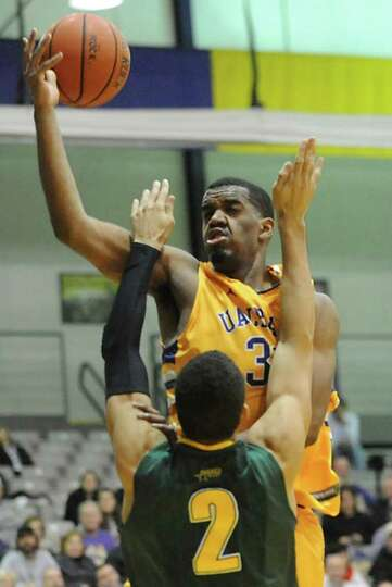 UAlbany's Jayson Guerrier is guarded by Luke Apfeld of Vermont as he drives to the basket during a b