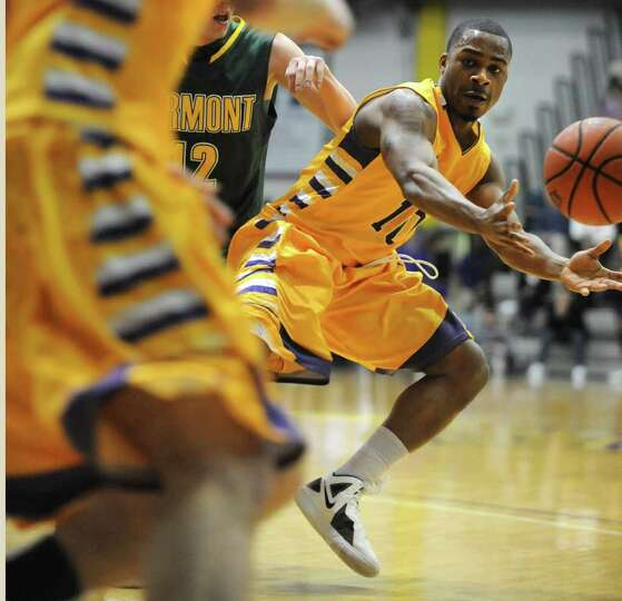 UAlbany's Mike Black hands off the ball during a basketball game against Vermont at SEFCU arena on W