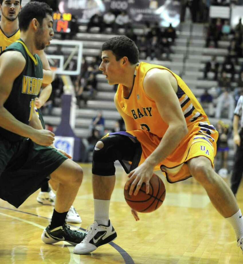 UAlbany's Logan Aronhalt dribbles the ball between his legs just before getting the ball stolen by Josh Elbaum of Vermont during a basketball game at SEFCU arena on Wednesday, Feb. 15, 2012 in Albany, N.Y.  (Lori Van Buren / Times Union) Photo: Lori Van Buren