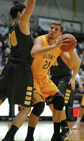 UAlbany's Blake Metcalf is guarded by Pat Bergmann of Vermont during a basketball game at SEFCU aren
