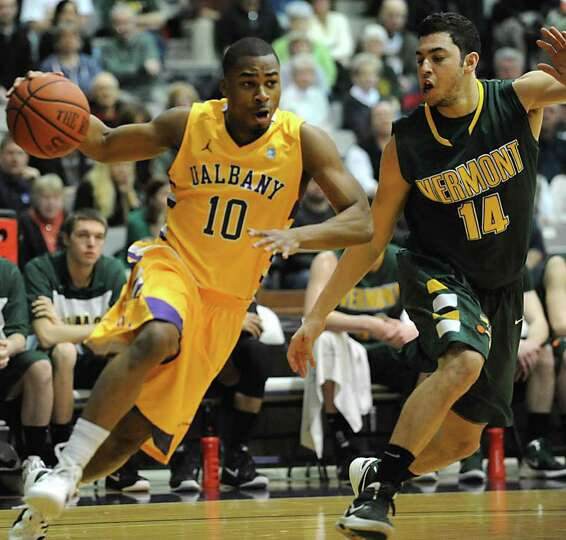 UAlbany's Mike Black is guarded by Josh Elbaum of Vermont as he drives to the basket during a basket